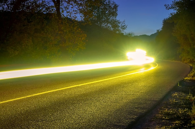 Faróis iluminam uma estrada vazia em uma floresta à noite de verão. trilhas longas e sinuosas