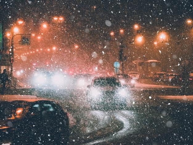 Faróis no tráfego da cidade no inverno à noite.