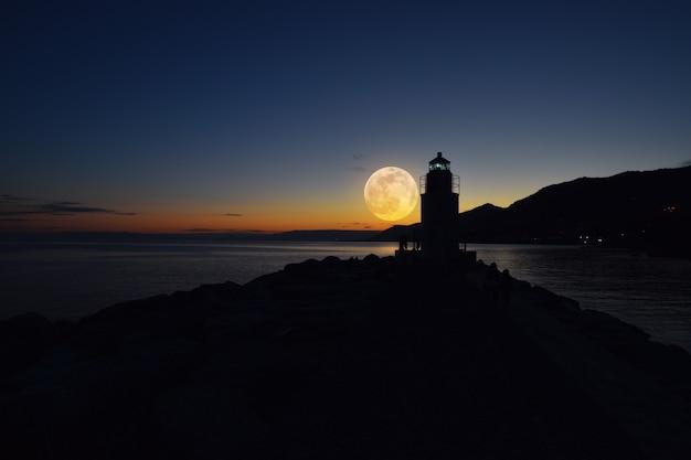 Farol à noite com lua cheia incrível sobre o mar