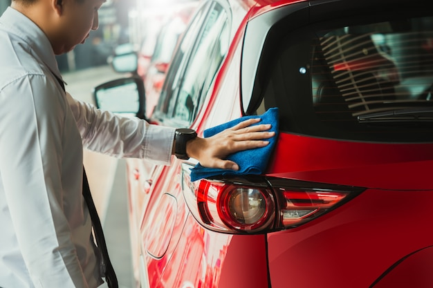 Farol asiático da inspeção do homem e lavagem de lavagem do equipamento do carro com carro vermelho para limpar à qualidade ao cliente na sala de exposições do carro da imagem automotivo do transporte automóvel do transporte do serviço.
