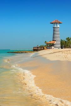 Farol branco vermelho listrado na costa do mar do caribe. república dominicana.