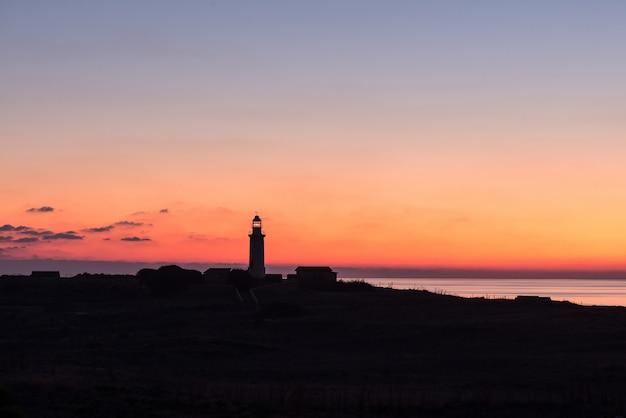 Farol com céu azul laranja e mar durante o pôr do sol