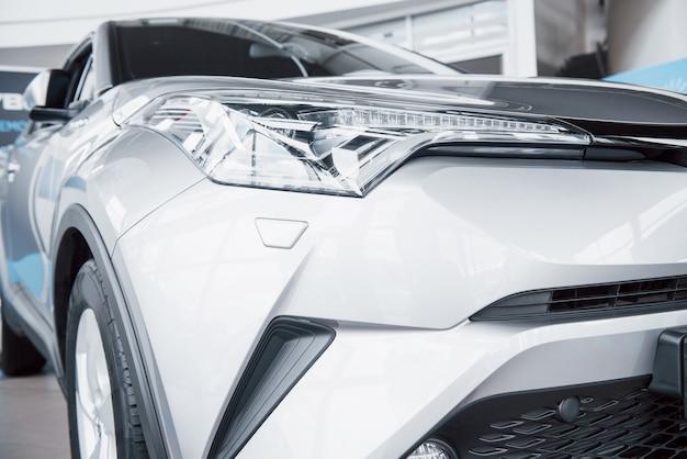Farol dianteiro com reflexos brilhantes da carroceria do carro.