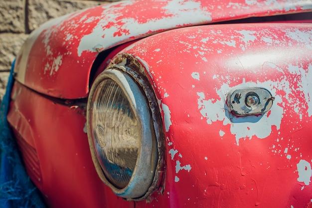 Farol dianteiro de um carro velho na garagem.