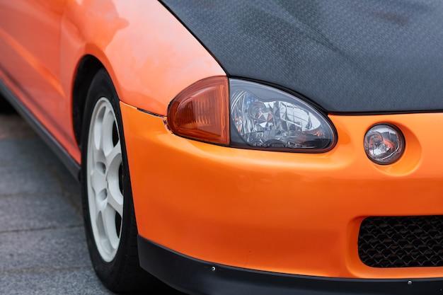 Farol dianteiro e volante de um carro esportivo