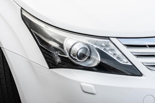 Farol do close up de um carro luxuoso branco.