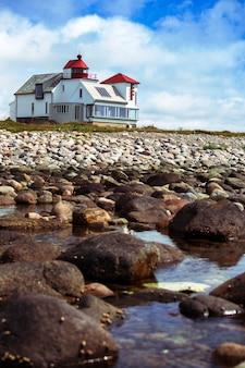 Farol e casas multicoloridas na costa de um fiorde, na noruega