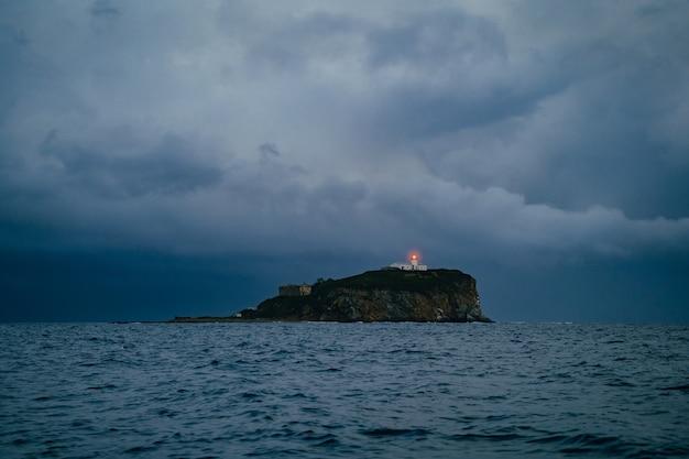 Farol em um mar nebuloso mostra a direção da solidão e do conceito de esperança