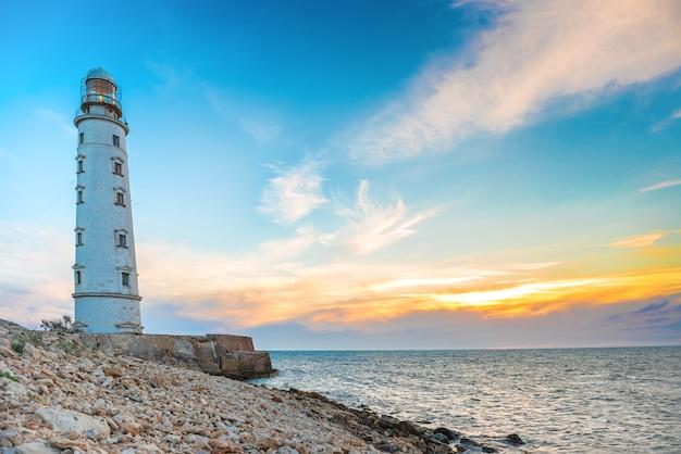 Farol na costa do mar com céu ao pôr do sol