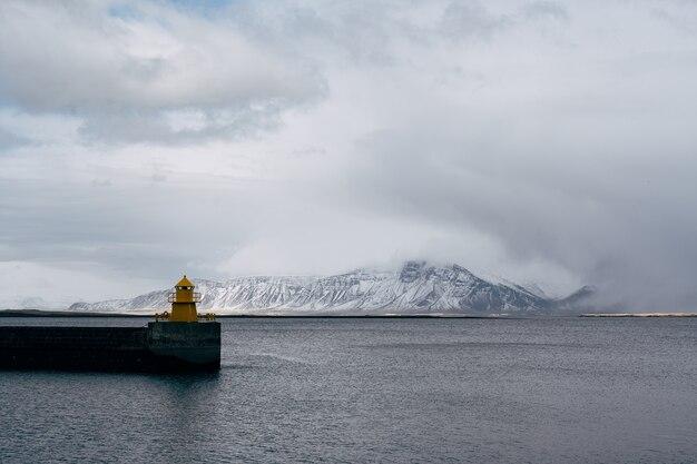 Farol no cais do mar em reykjavik islândia farol amarelo brilhante torre na costa do mar porto marítimo