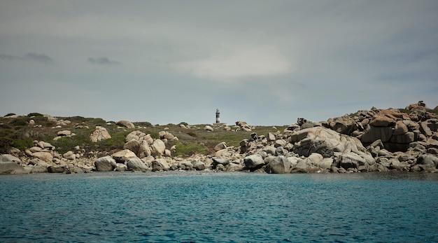 Farol no meio da paisagem rochosa da costa sul da sardenha