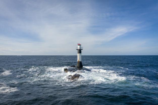 Farol no meio do mar sob o céu nublado