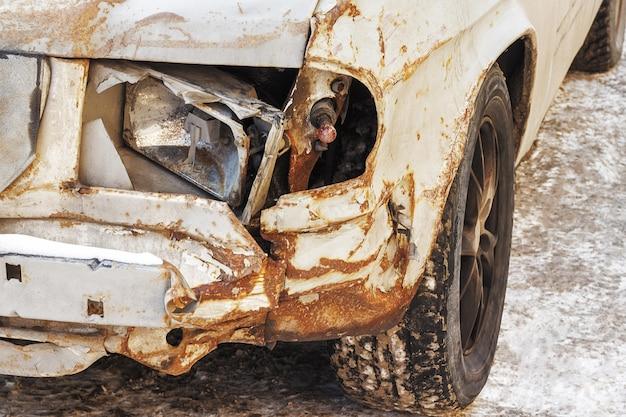 Farol quebrado e corrosão de metal em um carro velho