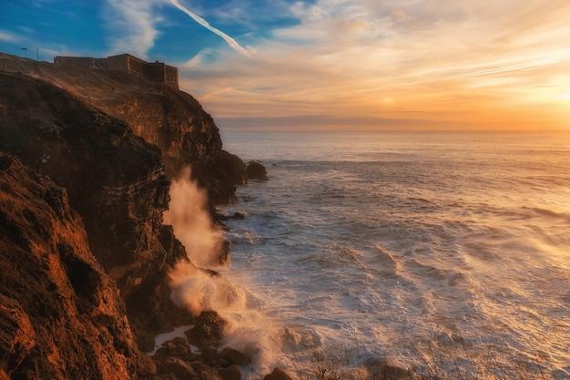 Farol sobre o oceano atlântico ao pôr do sol na cidade de nazaré, em portugal