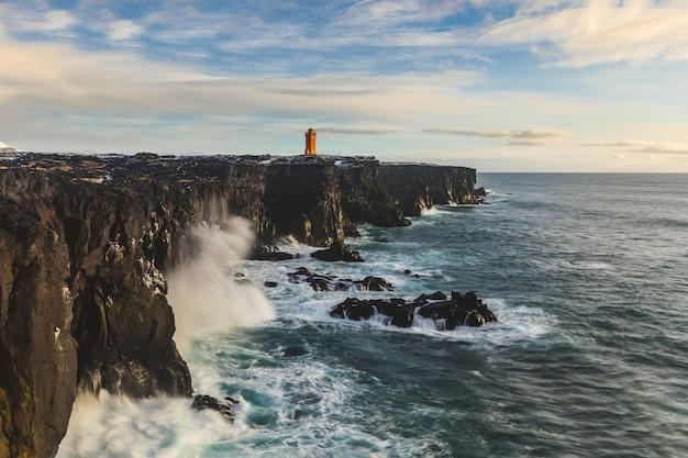 Farol sobre o penhasco, beira-mar do oceano na islândia