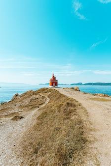 Farol vermelho na frente do oceano com ilhas no horizonte