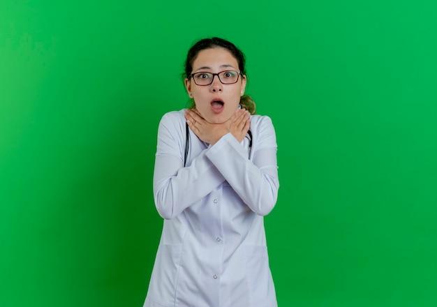 Farta da jovem médica vestindo bata médica, estetoscópio e óculos, sufocando-se, isolada na parede verde com espaço de cópia