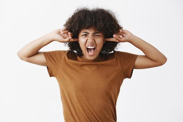 Farta de mulher jovem e elegante com penteado encaracolado, uma camiseta marrom cobrindo as orelhas com os dedos e gritando, carrancuda de aborrecimento e antipatia exigente irmão, desligue a música