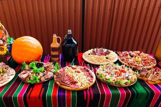 Farto buffet de aperitivos com pratos típicos de abóbora grande e drinque de festa de casamento