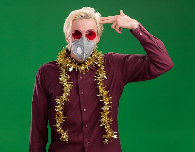 Farto de jovem loiro de óculos e máscara protetora com guirlanda de ouropel em volta do pescoço, olhando para a câmera, fazendo gesto de suicídio isolado sobre fundo verde