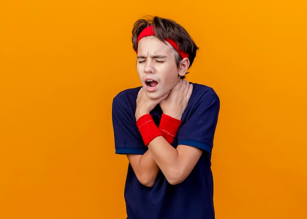 Farto de jovem rapaz bonito desportivo com bandana e pulseiras com aparelho dentário, de mãos cruzadas, sufocando-se com os olhos fechados, isolado na parede laranja