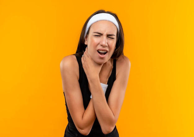 Farto de uma jovem e bonita desportiva com fita para a cabeça e pulseira a tentar sufocar-se na parede laranja