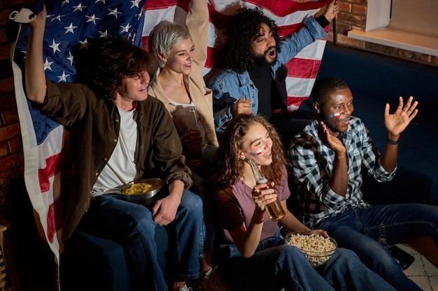 Fãs de amigos americanos assistindo a competições esportivas na tv juntos, gritando e gritando de felicidade, torcendo em casa no quarto escuro à noite