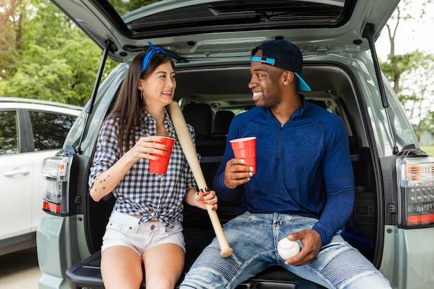 Fãs de beisebol sentados no porta-malas de um carro em uma festa ao ar livre