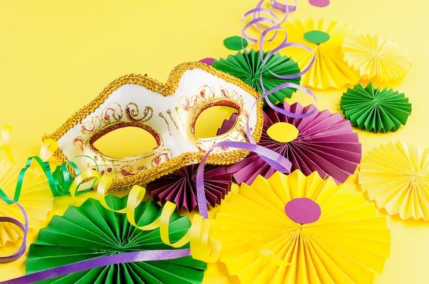 Fãs de carnaval colorido e máscara na mesa amarela