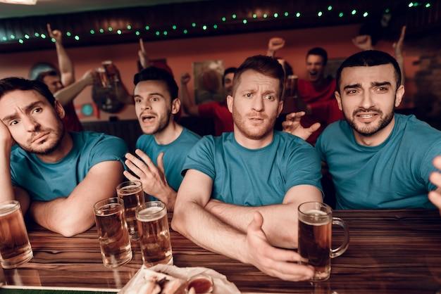 Fãs de equipe azul triste no bar no bar de esportes