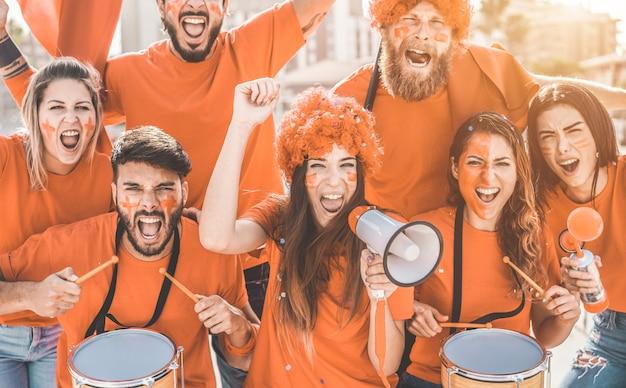 Fãs de esporte laranja gritando enquanto apoiam sua equipe fora do estádio