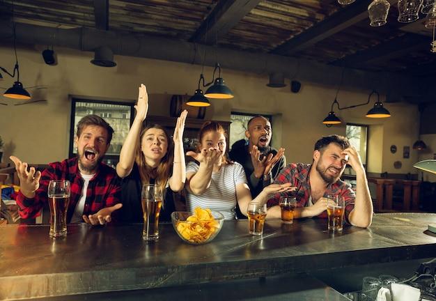 Fãs de esporte torcendo em bar, pub. tinir copos de cerveja enquanto assiste ao campeonato, competição. grupo multiétnico de amigos entusiasmados com a tradução. emoções humanas, expressão, conceito de apoio.