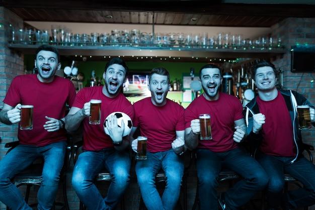 Fãs de esportes comemorando e bebendo cerveja no bar.