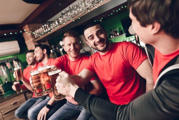 Fãs de esportes comemorando e torcendo bebendo cerveja