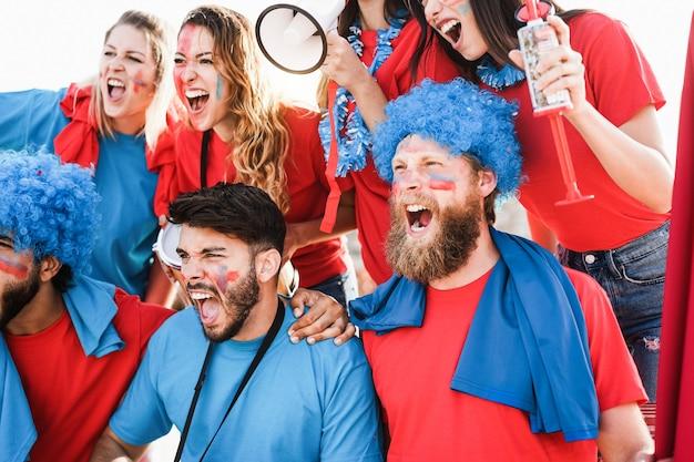 Fãs de esportes loucos gritando enquanto apoiam seu time - concentre-se no rosto do homem no centro