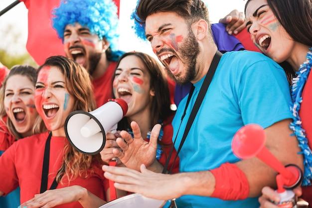 Fãs de esportes malucos tocando bateria e gritando enquanto torcem pelo time de futebol - foco principal no rosto do jovem direito
