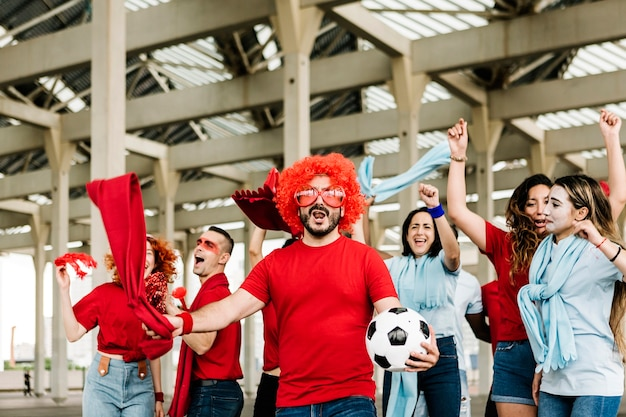 Fãs de esportes multirraciais felizes se divertindo fora do estádio