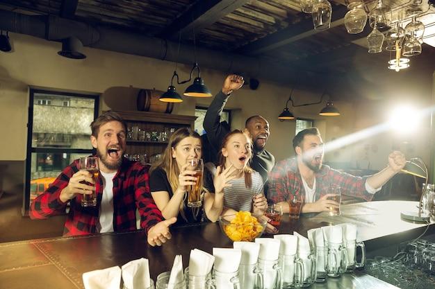 Fãs de esportes torcendo em um bar e bebendo cerveja durante a competição do campeonato