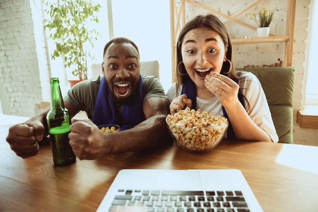 Fãs de futebol animados assistindo jogo de esporte em casa, suporte remoto do time favorito durante surto de pandemia de coronavírus