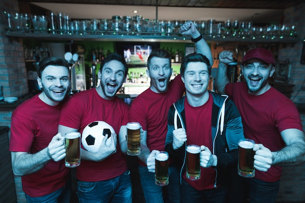 Fãs de futebol comemorando e bebendo cerveja.