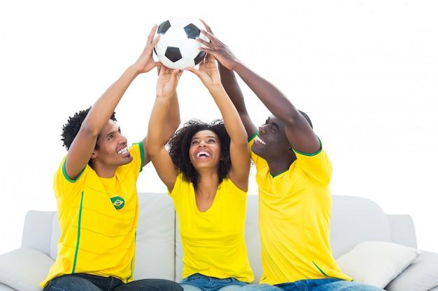 Fãs de futebol feliz em amarelo sentado no sofá com a bola