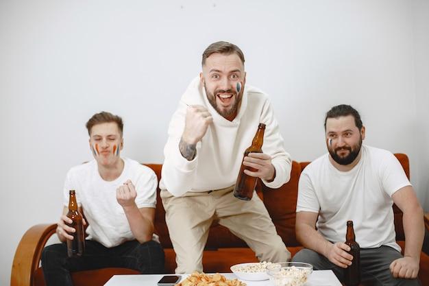 Fãs de futebol sentados no sofá da sala bebendo cerveja