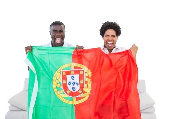 Fãs de portugal em êxtase sentado no sofá com bandeira