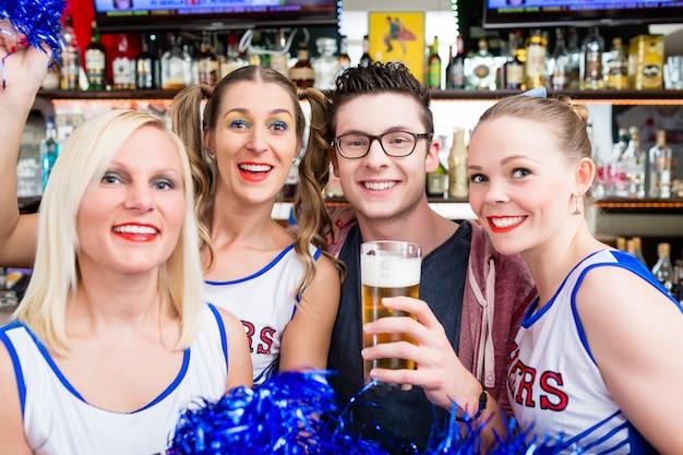 Fãs de uma equipe esportiva assistindo jogo no bar