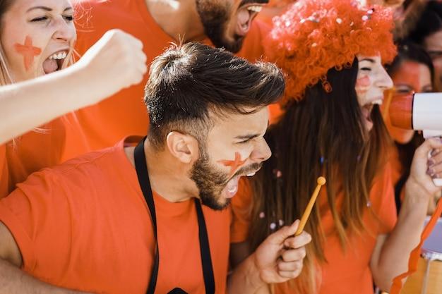 Fãs do esporte laranja gritando enquanto apoiam seu time fora do estádio - torcedores de futebol se divertindo no evento da competição - concentre-se no olho do homem