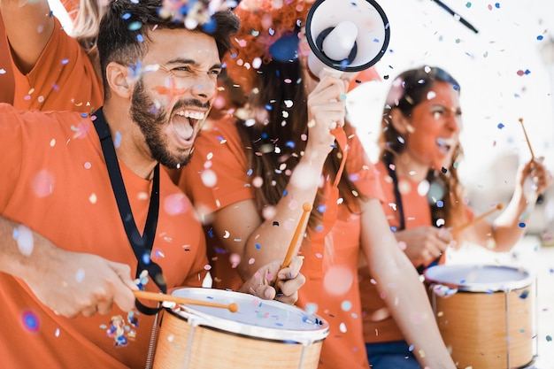 Fãs do esporte laranja gritando enquanto apoiam seu time fora do estádio - torcedores de futebol se divertindo no evento da competição - concentre-se no rosto do homem