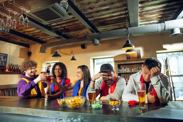 Fãs do esporte torcendo em bar, pub e bebendo cerveja durante o campeonato, a competição está acontecendo. grupo multiétnico de amigos.