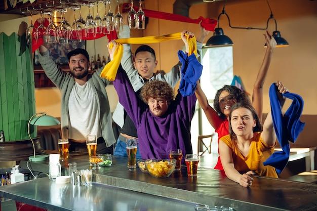 Fãs do esporte torcendo em bar, pub e bebendo cerveja enquanto assistem a uma competição esportiva.