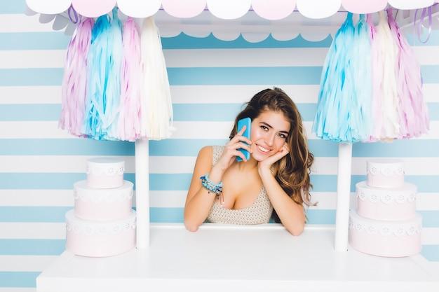 Fascinante garota alegre usando pulseira, falando no celular em pé atrás do balcão com bolos. adorável jovem com lindo sorriso, chamando a amiga durante a venda de sobremesas.
