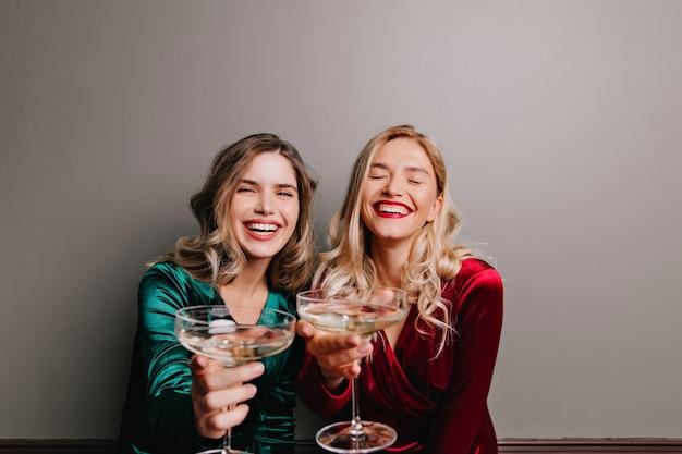 Fascinante garota caucasiana com vestido de veludo vermelho, bebendo champanhe. amigos felizes comemorando algo com vinho.